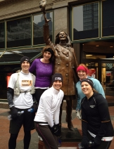 Runners in front of the Mary Tyler Moore statue in downtown Minneapolis